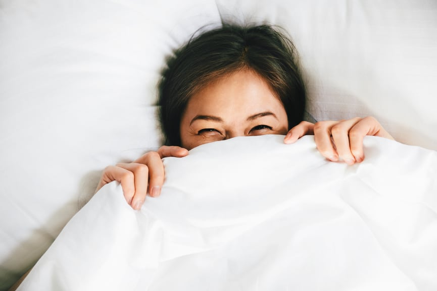 Smiling Female Covering Face With Blanket