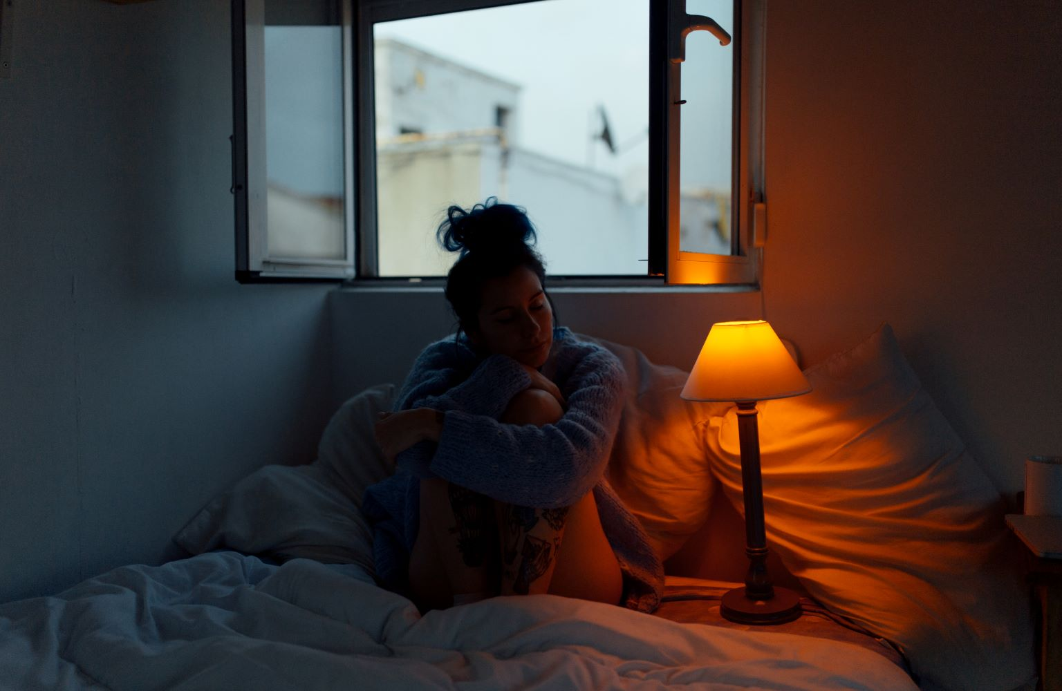 Traurig aussehende Frau in dunklem Zimmer sitzend auf einem Bett vor einem Fenster.