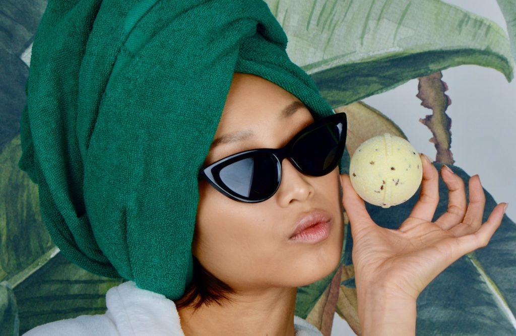 Frau mit Sonnenbrille, Handtuch auf dem Kopf und Tom Hemp's CBD Badekugel in gelb