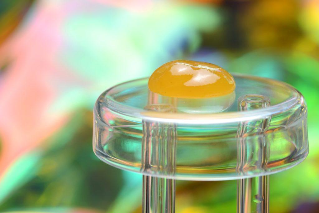 Gelbliches CBD Wax auf einem Glasgestell.